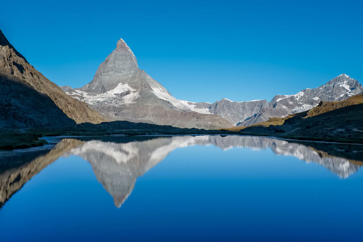 Scenic view of  matterhorn reflected in mountain lake against clear blue sky