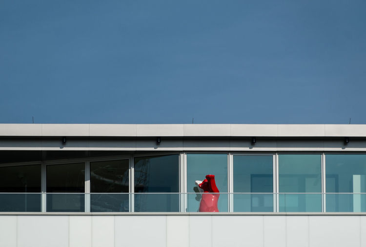 Red bear in balcony against clear sky