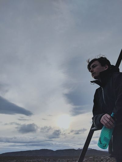Man looking away against cloudy sky during sunset