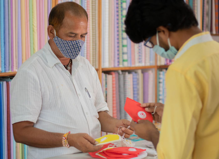 Midsection of young man buying flu mask at store