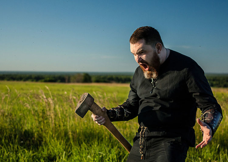 Angry man with axe standing on grassy field against sky