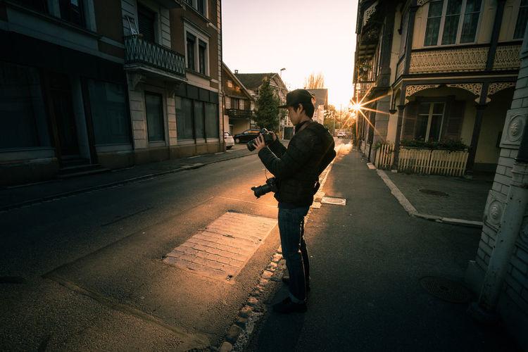 Man standing on sidewalk amidst buildings in city