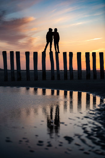 Silhouette men standing on wooden post by sea against sky during sunset