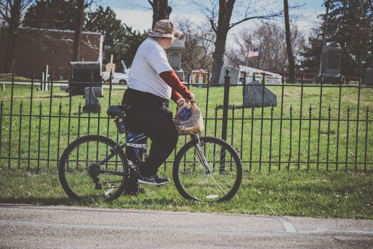 American Flag Bicycle Bike Black Iron Capture The Moment Cemetery Cool Hat Cute Exercise Graveyard Hat Iron Fence Looking Man One Man One Person Riding A Bicycle Riding A Bike  USA Untold Stories