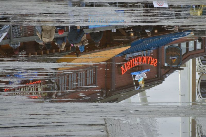 Reflection of man standing on wet glass in canal