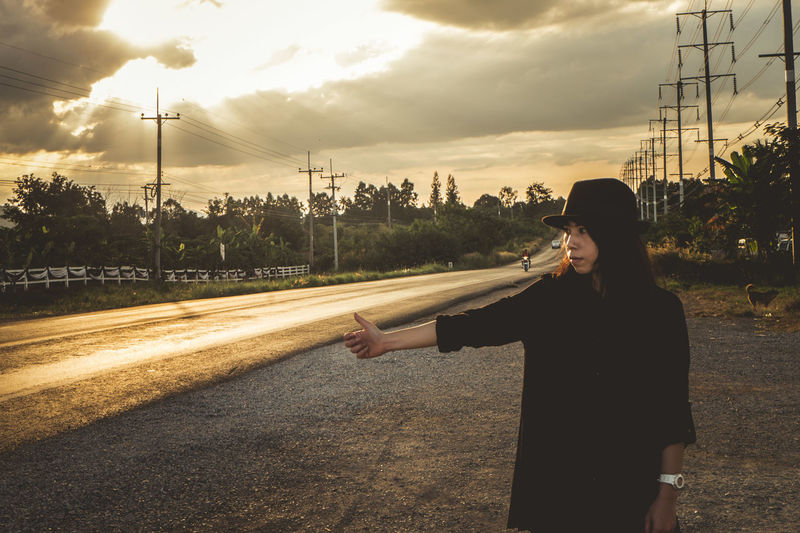 Woman standing on road against sky during sunset