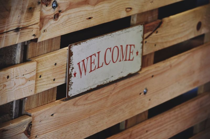 Welcome Sign On Wooden Railing