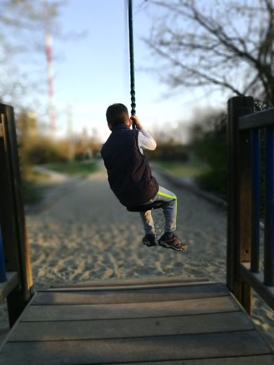 Rear View Of Boy Swinging On Swing At Playground
