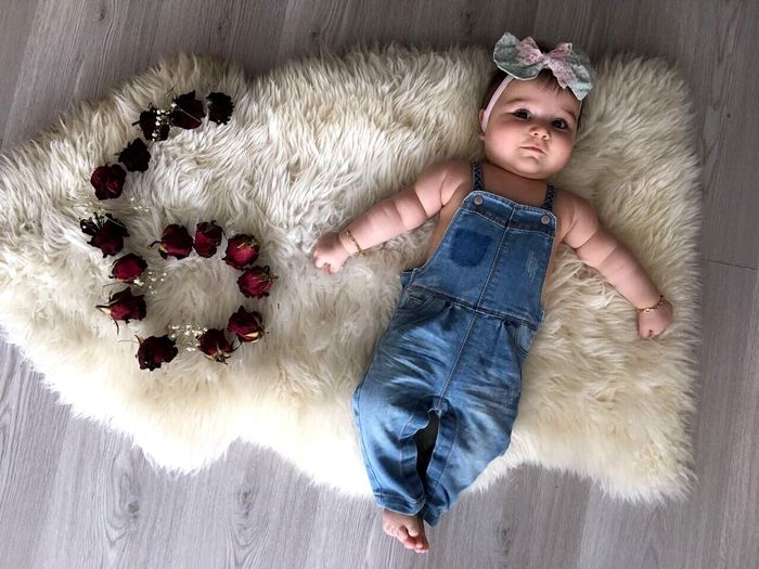 Directly above view of baby girl lying by red roses on white rug at home