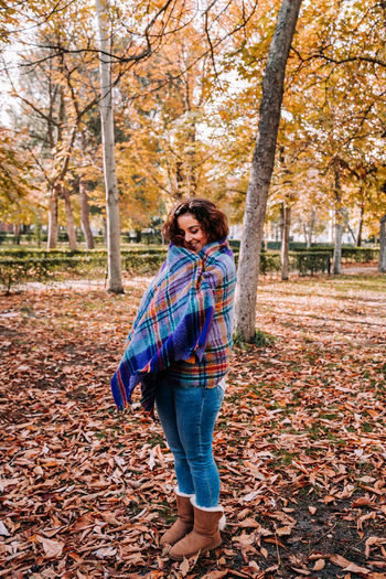 Smiling woman while standing by tree trunk during autumn
