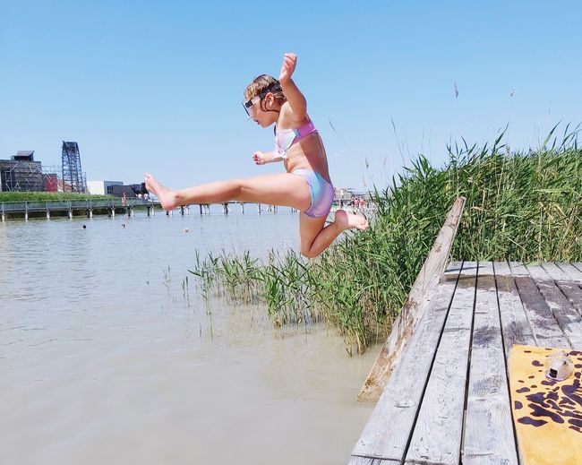 Full length of woman jumping in water against sky