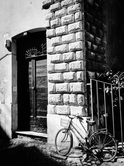 Bicycle against building in city