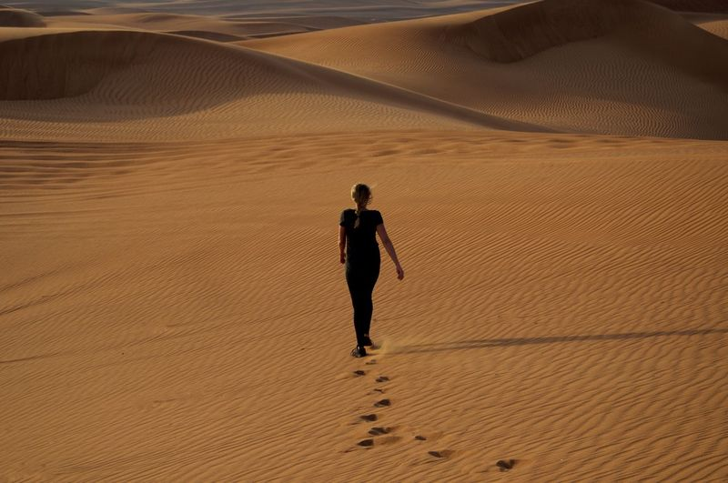 Rear view of woman walking on sand in desert