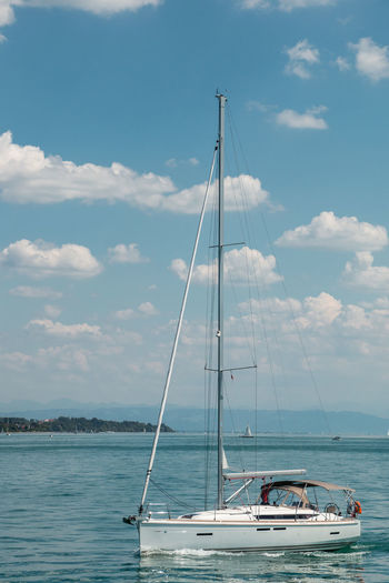 Nice little sailboat on a lake near the coast Nautical Vessel Transportation Water Cloud - Sky Sky Mode Of Transportation Sea Sailboat Waterfront Nature Day Pole Beauty In Nature Mast Sailing Travel No People Scenics - Nature Outdoors Yacht Luxury