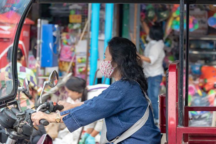 Side view of woman riding jinrikisha at market stall