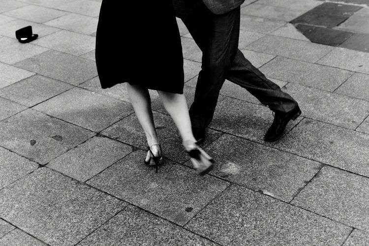 Low section of man and woman dancing on footpath