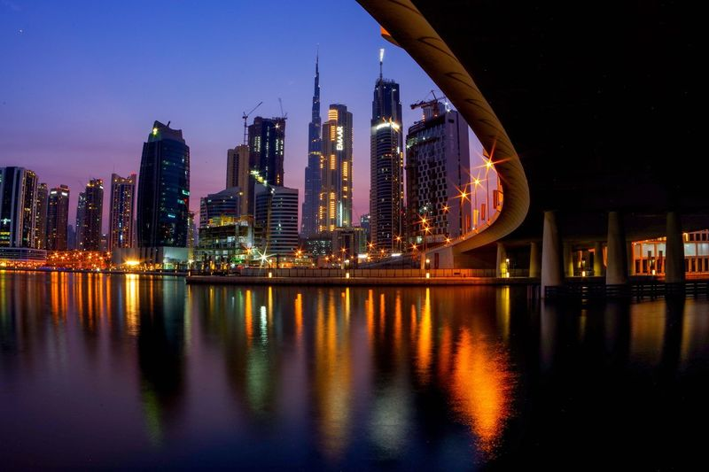 Illuminated Modern Buildings By River Against Sky In City At Night