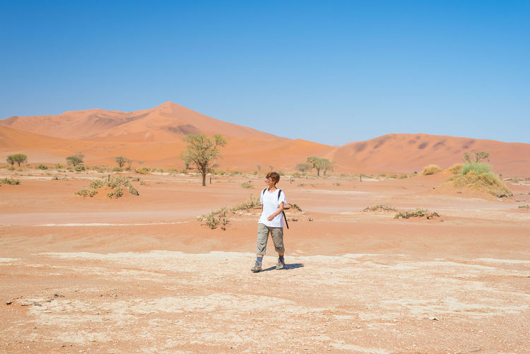 Hiker walking in namib desert against clear sky during sunny day