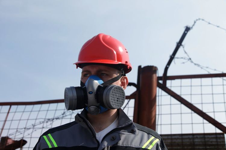 Close-up of worker wearing gas mask with fence in background against sky