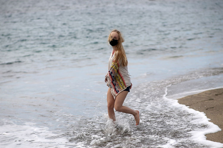 Full length of woman standing on beach