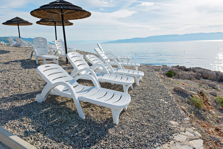 Pebble beach, chaise-longues and umbrellas in Istria, Croatian coast Beach Beauty In Nature Chair Day Horizon Over Water Nature No People Outdoors Relaxation Sand Scenics Sea Shore Sky Summer Sun Lounger Tranquility Vacations Water