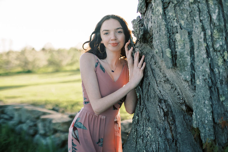 Portrait of smiling young woman standing on tree trunk