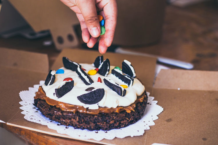 Cropped hand of person garnishing cake
