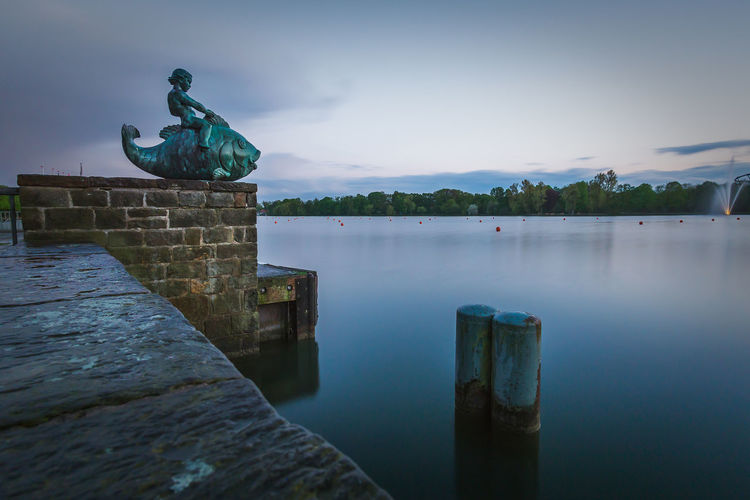 Puto auf dem Fisch am Maschsee Water Sky Architecture Art And Craft Built Structure Nature No People Representation Sculpture Day Waterfront Lake Outdoors Tranquility Cloud - Sky Statue Beauty In Nature Maschsee Hannover Germany EyeEmNewHere Long Exposure Evening Calm Water Landscape