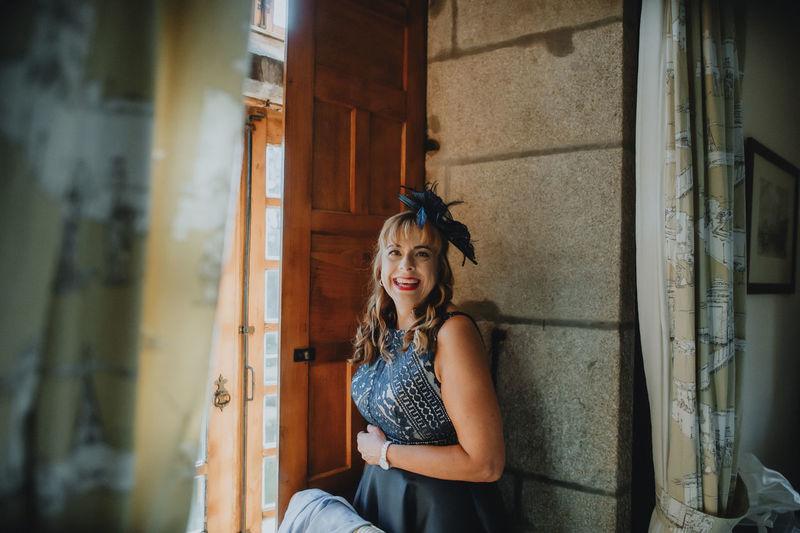 Portrait of smiling woman standing by door