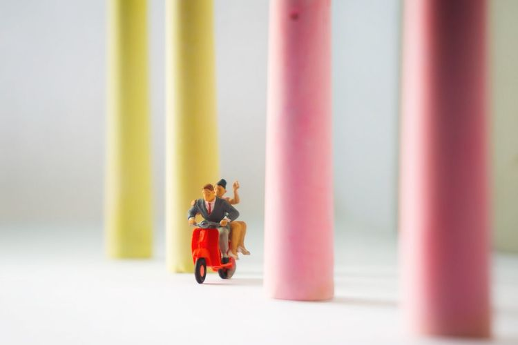 Close-up of figurines riding motor scooter by chalks on table