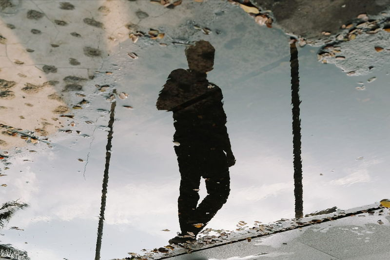 Reflection of man on puddle during rainy season