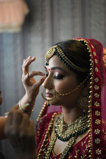 Beautician applying make-up to bride