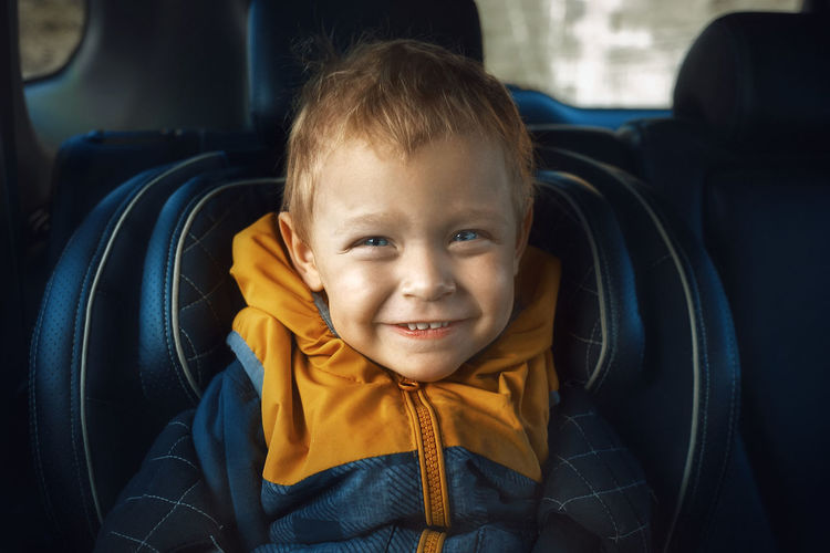 Close-up of smiling baby boy in car