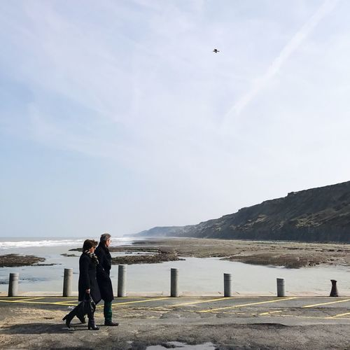 Walking near the sea Full Length Two Persons Woman And Man Couple Walking Lazy Sunday Leisure Activity Real People Lifestyles Sky Day Standing Outdoors Nature Men Water Sea Mountain Beauty In Nature Adult Adults Only