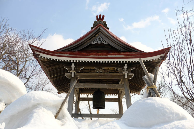 Low angle view of traditional building against sky during winter