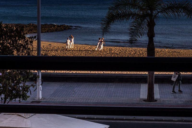 People on railing by sea