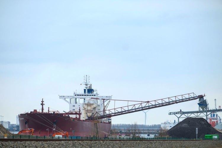 Doel, Antwerp, Belgium – February 2019: Large cargo ship unloading in the dock of the Antwerp harbor Sky Architecture Built Structure Nature Industry Ship No People Building Exterior Day Factory Transportation Freight Transportation Business Nautical Vessel Copy Space Water Outdoors Machinery Commercial Dock Shipping  Industrial District Industrial Equipment