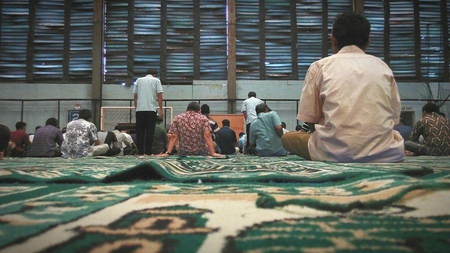 Rear View Of People Praying In Football Stadium