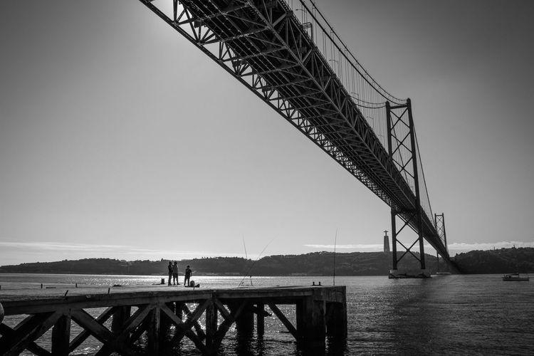 Distant view of men on pier at tagus river below april 25th bridge