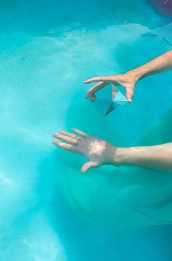 Cropped hand of woman holding pyramid crystal in swimming pool