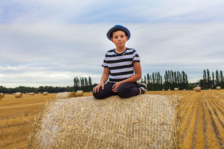 Agriculture Bale  Casual Clothing Day Farm Field Front View Hay Land Landscape Leisure Activity Looking At Camera Nature One Person Outdoors Plant Portrait Real People Rural Scene Sitting Sky The Modern Professional