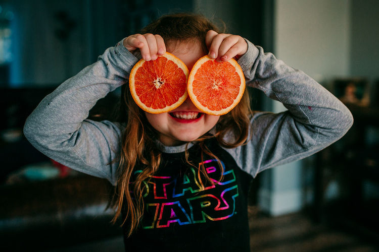 One Person Healthy Eating Front View Childhood Fruit Child Food Focus On Foreground Food And Drink Wellbeing Freshness Casual Clothing Holding Orange Color Orange SLICE Citrus Fruit Portrait Innocence Obscured Face Star Wars