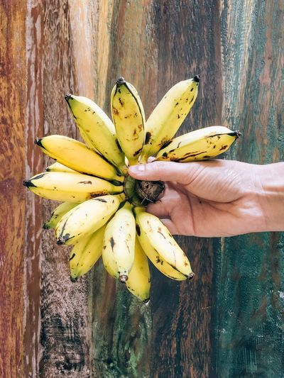 Cropped hand holding banana against wood