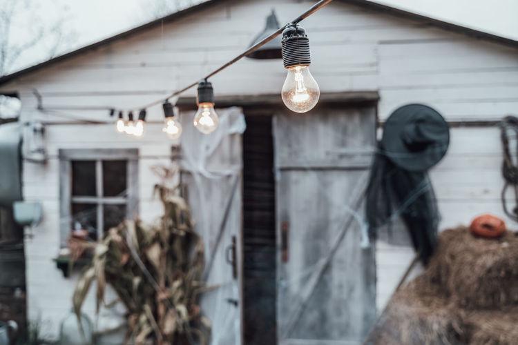 Illuminated light bulbs hanging on wall of building