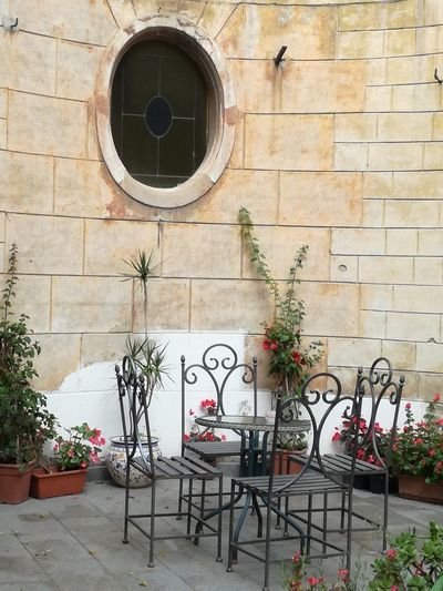 Simple Moment Garden Iron Chair Chairs And A Table Outdoors Wall Oval Window Style Old Places No People