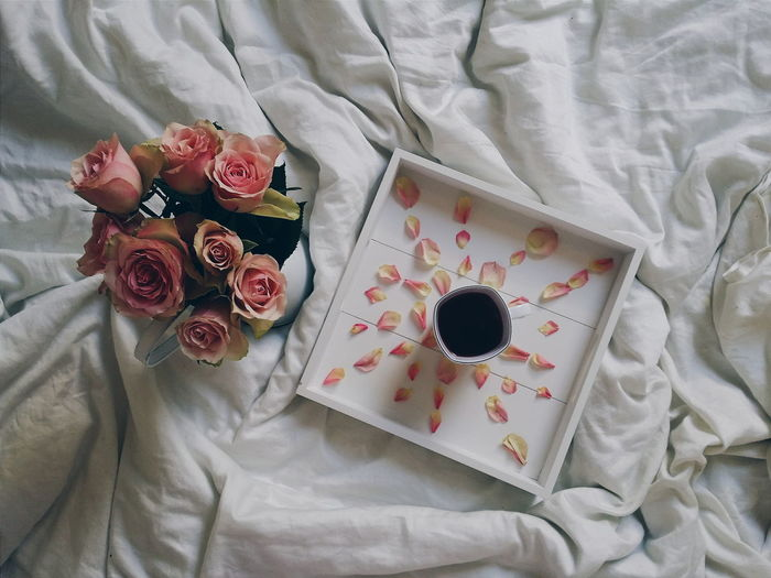 High angle view of black tea along with roses on wrinkled sheet