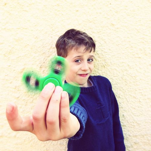 Portrait of boy playing with green fidget spinner against wall