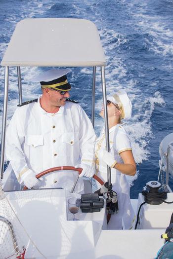 Sailors sailing ship on sea