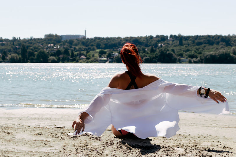 Back view of carefree woman with arms outstretched relaxing at the beach in summer day.