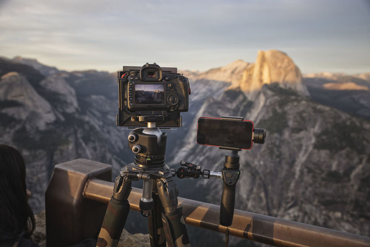 Close-up of camera against mountain range
